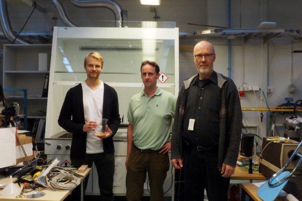 Konsta Turunen, Ari Seppälä och Kari Saari jobbar i labbet med HeatStock. Turunen håller i en kompositblandning.