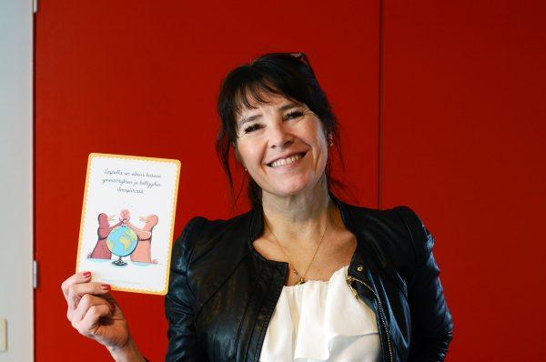 Lotta Uusitalo-Malmivaara med ett kort i handen som ska med i moderskapsförpackningen.
